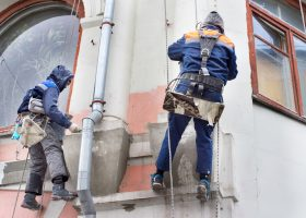 two construction workers hanging on a rope from a tall building